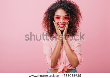 Engaging black girl in yellow shirt posing with surprised face expression. Indoor portrait of stunning lovely woman with african hairstyle wears colorful sunglasses.