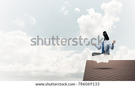 Faceless businessman with camera zoom instead of head sitting in lotus pose #786069133