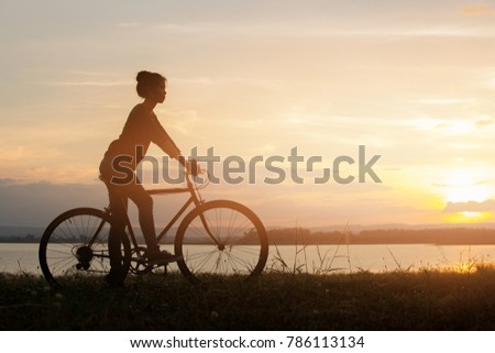 girl riding bicycle at sunset or sunrise background #786113134
