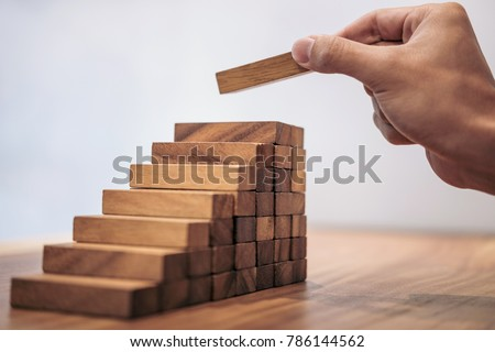 Alternative risk concept, plan and strategy in business, Risk To Make Business Growth Concept With Wooden Blocks, hand of man has piling up and stacking a wooden block. #786144562