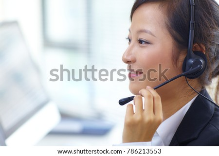 young asian woman working in front of computer with headset in the call centre #786213553
