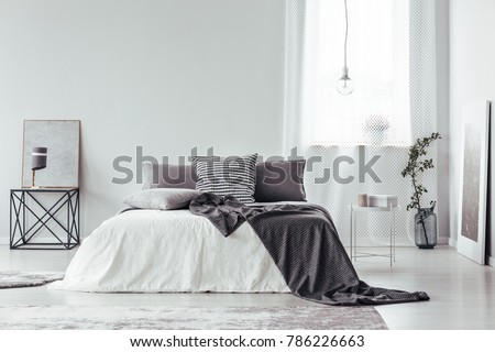 Simple, gray and white bedroom interior with blanket and pillows on king size bed, bright window and posters #786226663