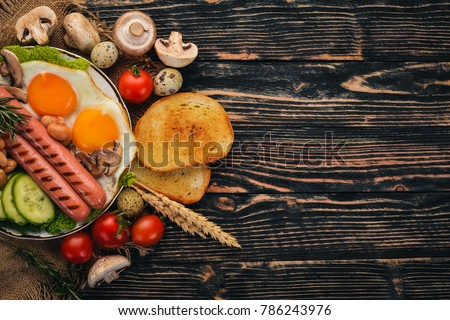English breakfast - fried egg, beans, tomatoes, mushrooms, bacon and toast. Top view. On a wooden background. #786243976