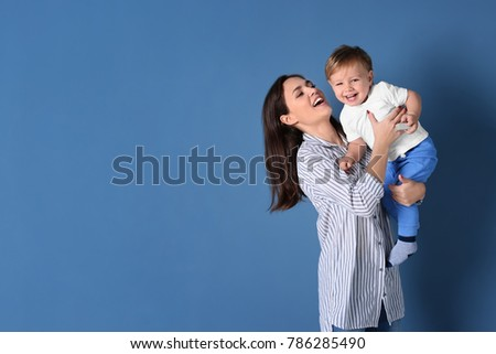 Beautiful young woman with her baby on color background