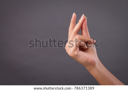 hand snapping finger snap studio isolated; yes, ok, accepting hand, finger snapping for good creative idea; conceptual woman hand snap action gesture concept; woman hand talent model studio isolated Royalty-Free Stock Photo #786371389