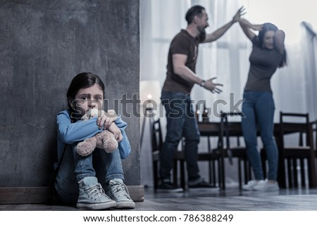 Unhappy childhood. Nice unhappy cheerless girl sitting on the floor and holding her toy while listening to her parents fight #786388249