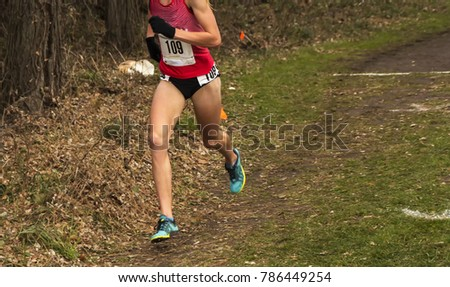 A female cross country runner is racing in the woods trying to hold on to first place at a high school race. #786449254