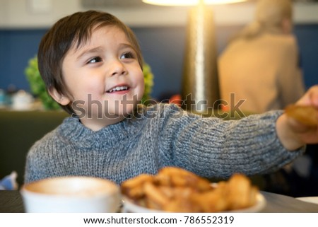 Happy Little boy eating french fries for his snack at the restaurant , Cute toddler boy sitting and eat patato chips with parent for their diner. Happy and Healthy child concept #786552319