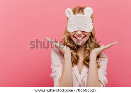 Studio shot of pleased beautiful young woman posing in eyemask. Cheerful european girl in pajamas standing on pink background in sleep mask in morning. #786606529
