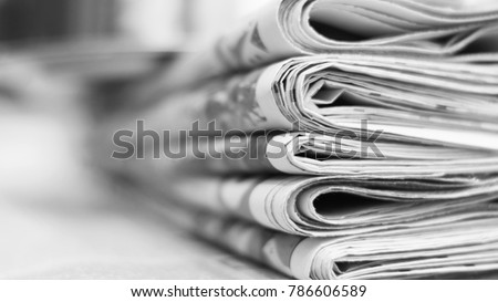 Pile of fresh morning newspapers on the table at office. Latest financial and business news in daily paper. Pages with information (headlines, articles, photos, text). Folded and stacked journals Royalty-Free Stock Photo #786606589