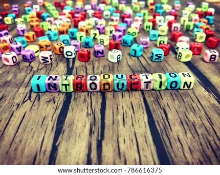 INTRODUCTION word of colourful cube alphabet on wooden table. #786616375