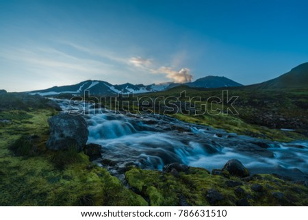 Picturesque waterfall flowing over rocks in the Kamchatka Peninsula, Russia with a distant volcano with a plume of steam #786631510