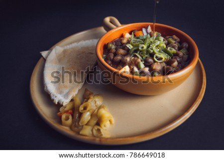 A high angle color studio image of Egyptian, Arabian, Middle Eastern Traditional food (Fava Beans with Vegetables/Green Paprika) A.K.A (Foul) - Also served in Lebanon and most of Arabian countries. #786649018
