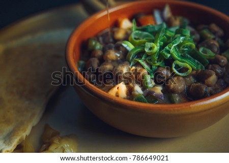 A close up color image of Egyptian, Arabian, Middle Eastern Traditional food (Ful/Fava Beans with Vegetables/Green Paprika) A.K.A (Foul) - Also served in Lebanon and most of Arabian countries. #786649021