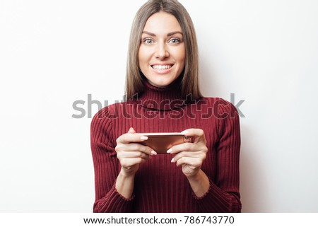 Indoor shot of a beautiful young brown-haired woman, isolated on white background, looking at smartphone, smiling openly, holding smartphone in both hands. Looks at the phone and smiles #786743770