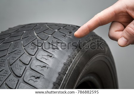 Man's hand finger pointing to the old, damaged and worn black tire tread. Change time. Tire tread problems and solutions concept. Royalty-Free Stock Photo #786882595