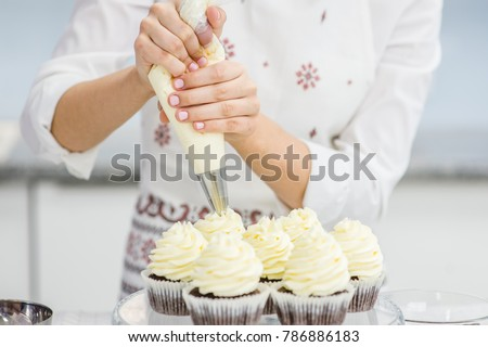Close up hands of the chef with confectionery bag squeezing  cream on cupcakes Royalty-Free Stock Photo #786886183