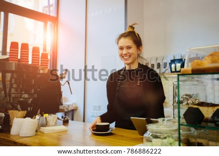 Beautiful hipster female barista with a two cups on coutner, looking away and smiling to someone while standing near the bar counter in modern cafe interior. #786886222