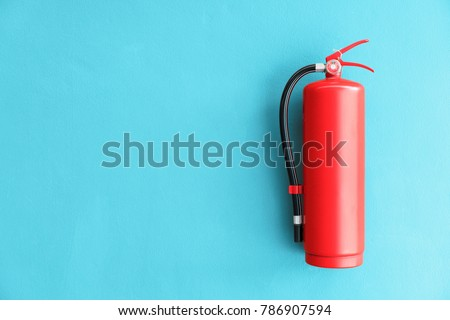 Fire extinguisher on the blue wall background.