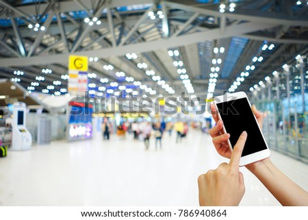 Hand holding mobile phone with airport terminal blurred crowd of Travelling people on the background, Bokeh light, Social network, internet,Traveling concept #786940864