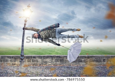 Man gets blown away by a storm Royalty-Free Stock Photo #786975550