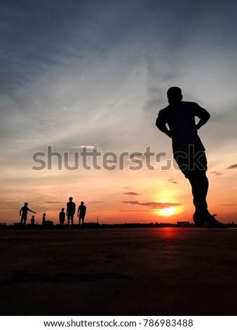 Silhouette of people exercising at a riverside park before the sunset