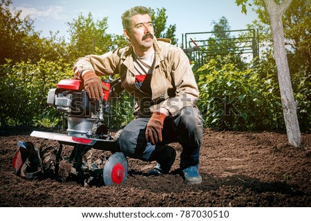 Happy man Farmer plows the land with a cultivator, preparing it for planting vegetables, on a sunny day garden #787030510