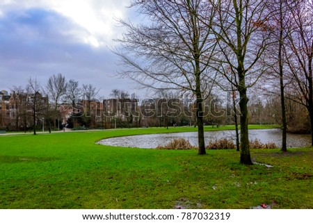 Brown stone houses with trees in foreground under autumn winter rainy sky.   #787032319