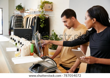 Man and woman working behind the counter in a clothing store Royalty-Free Stock Photo #787054072