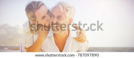 Man giving his smiling wife a piggy back at the beach on a sunny day Royalty-Free Stock Photo #787097890