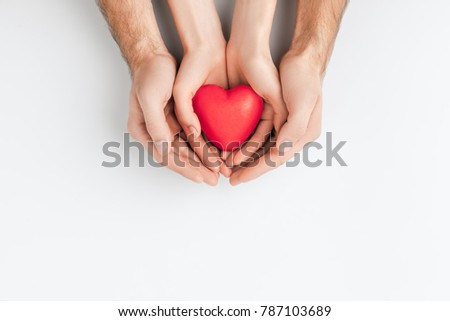 top view of hands of elder person and smaller one holding red heart isolated on white background    #787103689