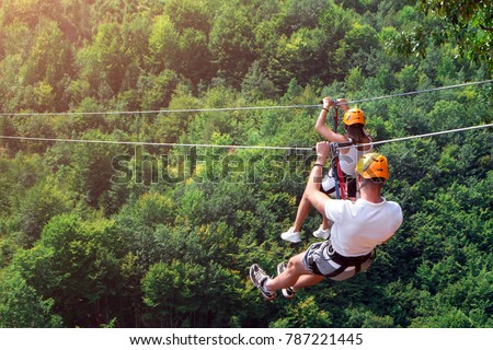 Zipline is an exciting adventure activity. Man and woman hanging on a rope-way. Tourists ride on the Zipline through the canyon of the Tara River Montenegro. Couple in helmets is riding on a cable car #787221445