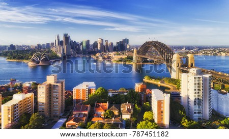 Sunlight on a bright sunny day on major Sydney city and Australia landmark around sydney harbour from Kirribilli suburb on north shore towards CBD high-rise towers across blue water. #787451182
