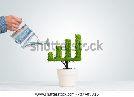 Hand of man watering small plant in pot shaped like growing graph #787489915