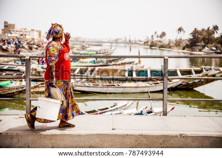 Woman walking across bridge after buying her fish for the day in St.Louis, Senegal. #787493944