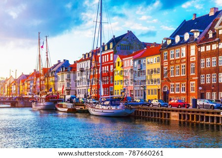 Scenic summer sunset view of Nyhavn pier with color buildings, ships, yachts and other boats in the Old Town of Copenhagen, Denmark #787660261