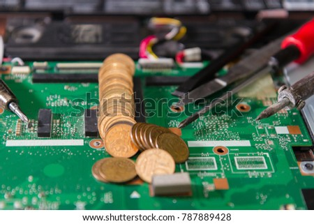 printed circuit board green with tools and coins closeup. repair of notebook components #787889428