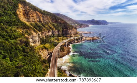 Sea cliff bridge at the edge of steep sandstone cliff on the Grand Pacific drive along pacific coast of Australia, NSW. Aerial view towards distant hill ranges on sunny summer day. #787893667