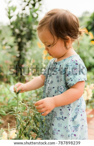 Close Up Little Girl Picking Flowers in Meadow #787898239