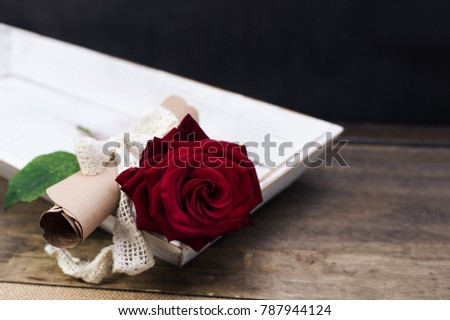 surprise for St. Valentine's Day on a table: red rose and a message on papyrus vintage paper with a ribbon.  #787944124