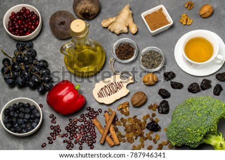 Food sources natural antioxidants. Antioxidants neutralize free radicals, have beneficial health effects. Group includes minerals, carotenoids and vitamins. Small board with word antioxidant. Top view #787946341