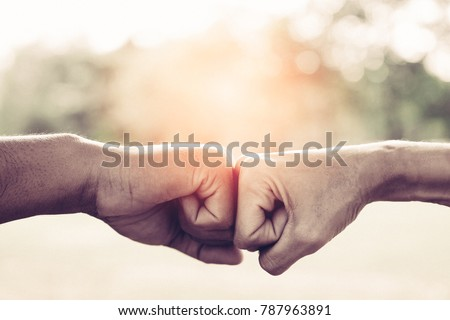 A close up image of a fist bump in vintage tone. Hands of young people show strength teamwork in the nature, team concept. #787963891
