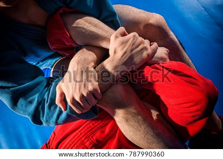 Close-up two wrestlers of grappling and jiu jitsu in a blue and red kimono makes armbar .Submission wrestling   on blue tatami Royalty-Free Stock Photo #787990360