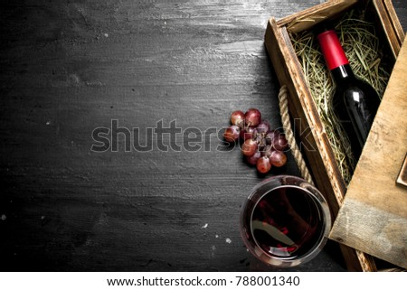 bottle of red wine in an old box with a branch of grapes. On the black chalkboard.