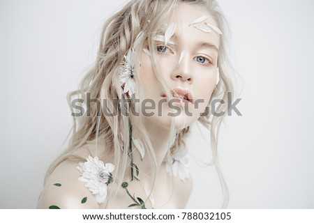 Beautiful young woman with petals of chrysanthemum on face and body. Beauty, natural cosmetics concept. #788032105