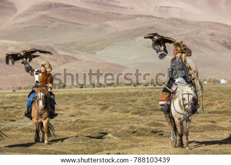 SAGSAY, MONGOLIA - SEP 28, 2017: Kazakh Eagle Hunter (Berkutchi) with horse teaches his daughter to hunting to the hare with a golden eagles in the mountains of Bayan-Olgii aimag.  #788103439