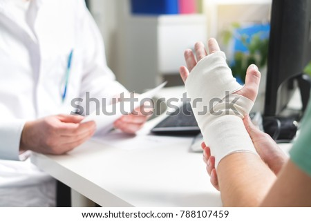 Injured patient showing doctor broken wrist and arm with bandage in hospital office or emergency room. Sprain, stress fracture or repetitive strain injury in hand. Nurse helping customer. First aid. #788107459