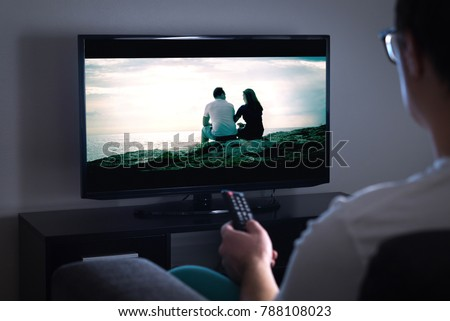 Man watching tv or streaming movie or series with smart tv at home. Film or show on television screen. Person holding the remote control or switching channel. Turning on or off tv.  #788108023
