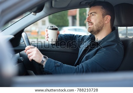 Man drinking coffee while driving the car #788210728