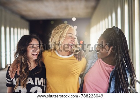 Laughing group of diverse young girlfriends having fun while walking together down a walkway in the city at night #788223049